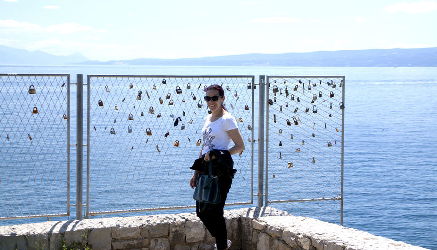 Woman standing by love locks on fence against sea and sky