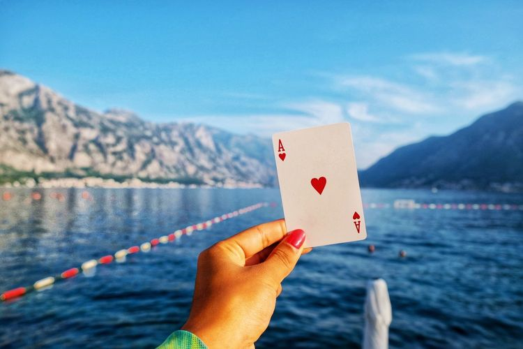 Cropped hand of woman holding playing card while on sea against sky
