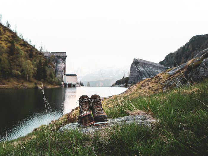 Scenic view of boots against an old dam between mountains