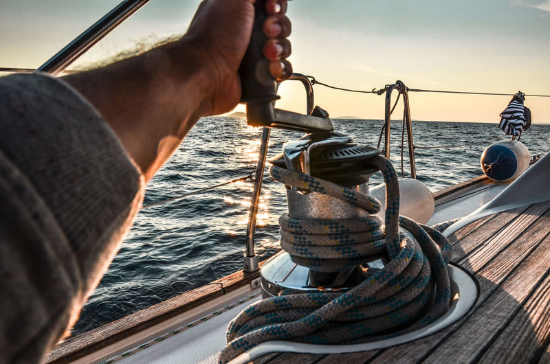 Cropped hand of man rigging rope on boat in sea against sky during sunset