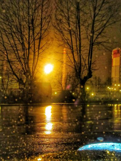 Fire and rain at night Architecture Bare Tree Explosion Fire Flame Gas Leakage Gasometer Illuminated Industrial Photography Learn & Shoot: After Dark Light And Shadow Night Photography Rain Rain Reflection Water Wet Lumicar