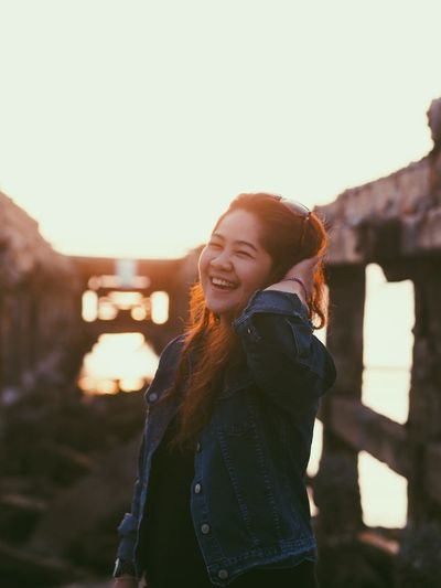 Portrait of cheerful woman standing at beach during sunset