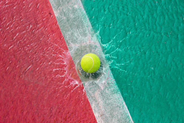 High Angle View Of Yellow Ball Splashing Into Water