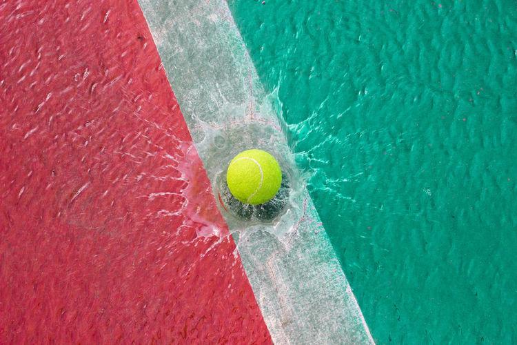 High angle view of yellow ball splashing into water