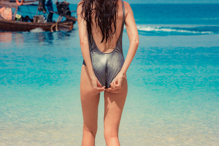 Woman wearing swimsuit standing on shore at beach
