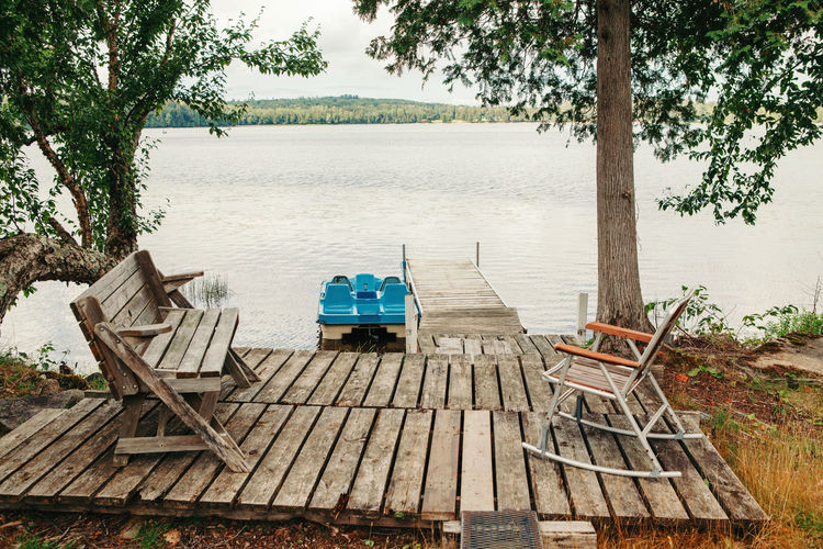 Empty chairs by lake against trees