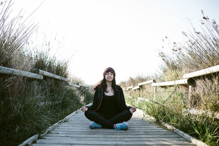 Woman Meditating On Boardwalk Amidst Grass