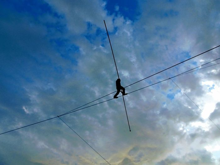 Balance Balancing Act Blue Cable Circus Cloud - Sky Clouds Day EyeEm Selects Low Angle View Man Outdoors Silhouette Sky Walking The Line