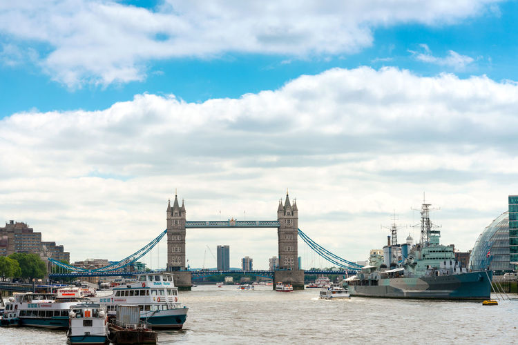 Boats and ship sailing on thames river by tower bridge against sky