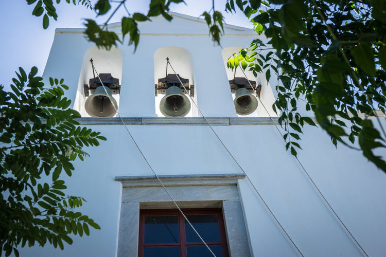 Low angle view of three bells on a chapel
