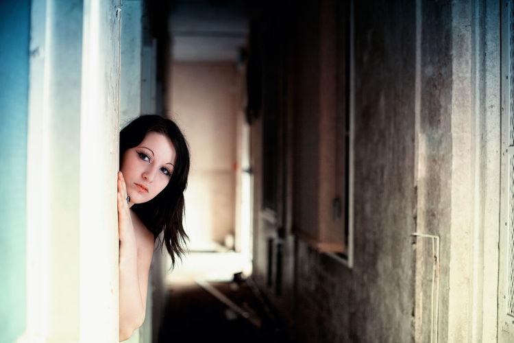 Portrait of woman standing behind door