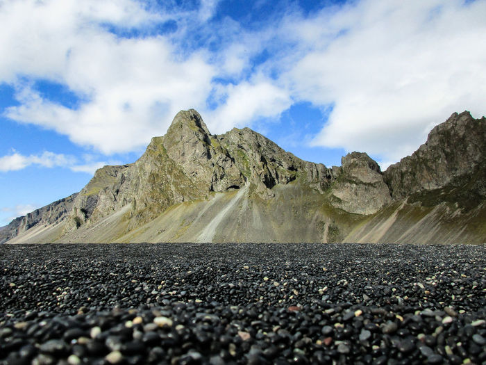 Surface level of stones on road against sky
