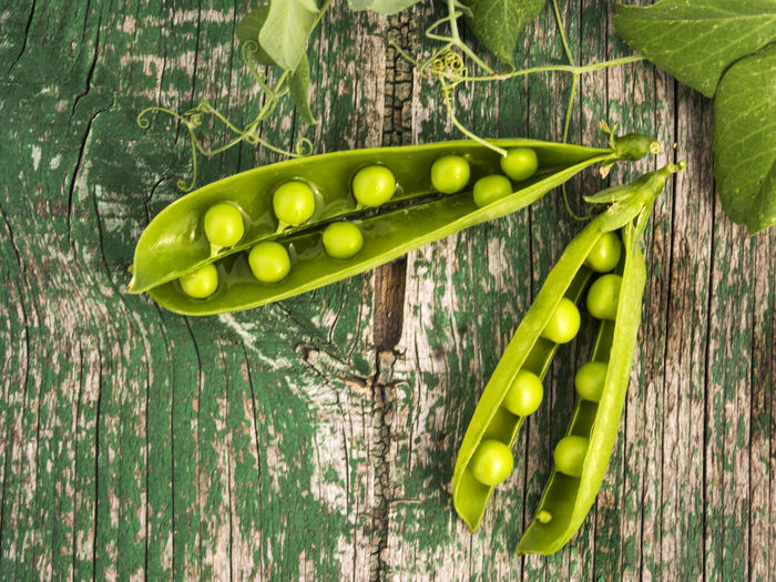 High angle view of green peas on weathered wooden table