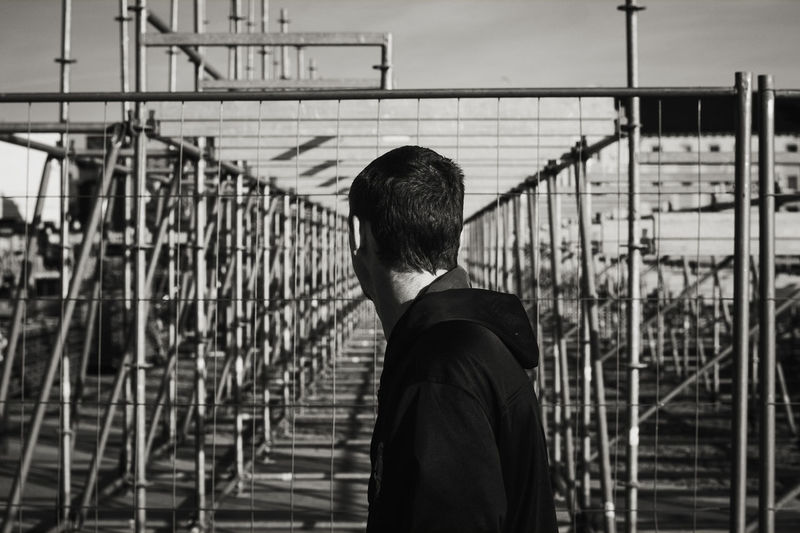 Man standing by railing against sky