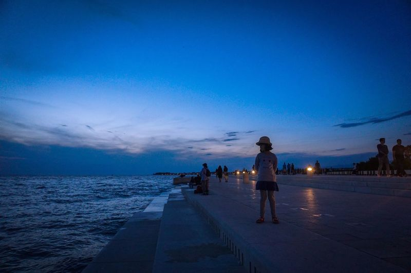 People on beach in city at night