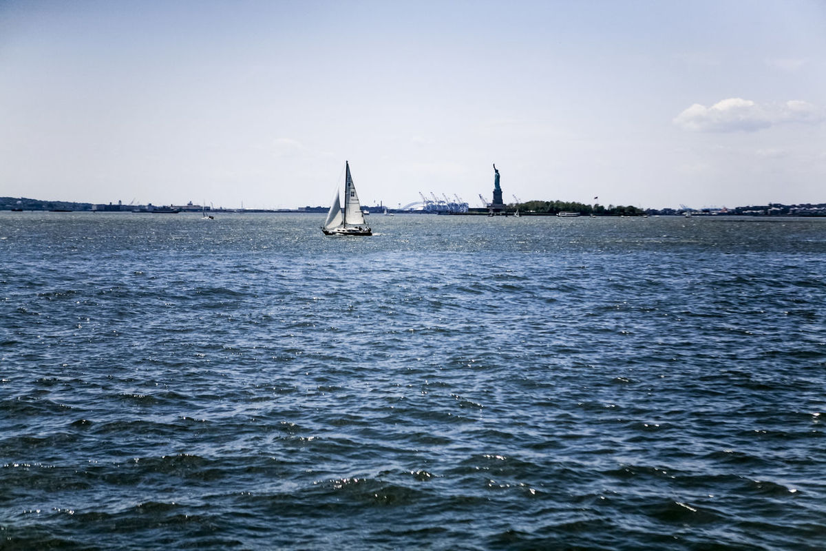 Boat Distant Escapism Hudson River Lake Mode Of Transport Moored Nautical Vessel Outdoors Reflection Rippled River Riverside Sailboat Sailing Sea Sky Statue Of Liberty Transportation Tropical Climate Vacations Water Waterfront Weekend Activities Yacht