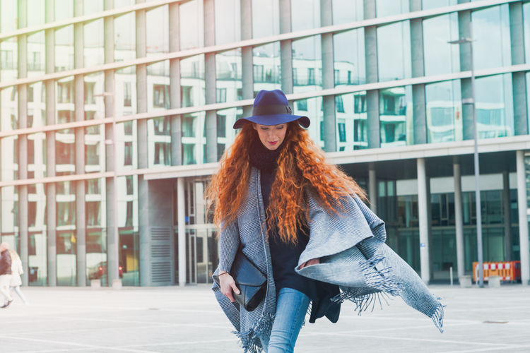 Young Woman Wearing Hat While Walking On City Street