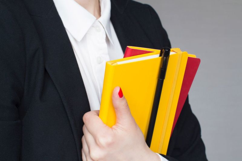 Young woman in white shirt and black suit holding red and yellow notebooks Notes Working Hard Busy Planner Notebook Female Red Nail Polish White Shirt Stylish Suit Boss Classical Style Power Office Strongwoman Business Woman One Person Holding Business Adult Close-up Suit Yellow Business Person Well-dressed Menswear Midsection Studio Shot