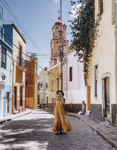 A young woman wearing in the streets of a colorful mexican town.