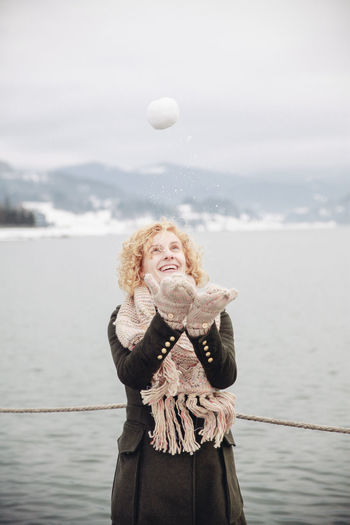 Happy Woman Playing With Snowball By Lake Against Sky