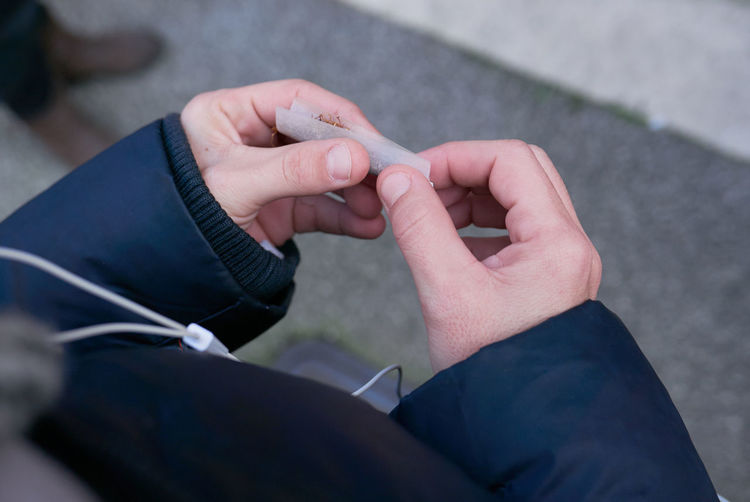 High angle view of person rolling joint outdoors