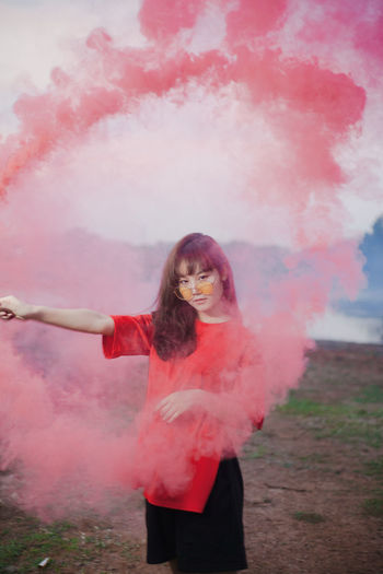 Model with red smoke Adult Arms Raised Casual Clothing Fashion Front View Hairstyle Hand Holi Human Arm Leisure Activity Lifestyles Limb Looking At Camera One Person Outdoors Pink Color Portrait Real People Smoke - Physical Structure Standing Three Quarter Length Women Young Adult Young Women