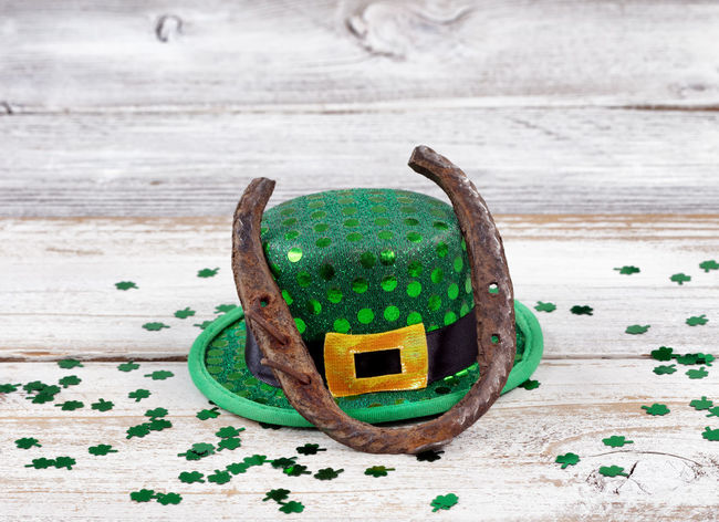 Close up view of a rusty horseshoe resting on hat for St Patrick day with shiny clovers on weathered white wooden boards Clover Hat Holiday Horseshoe Luck St Patrick's Day Irish St Patrick Wood - Material