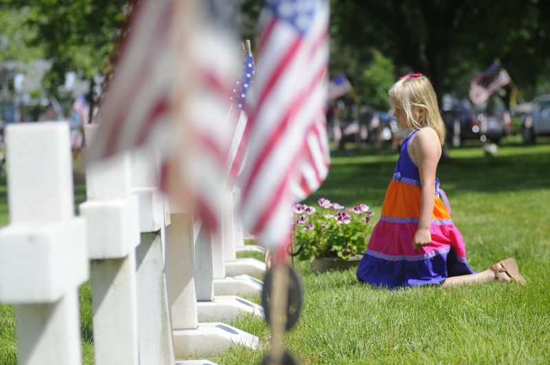 Young blonde girl in a colorful dress kneels at a soldiers headstone as the cemetery is decorated for a holiday Blonde Kids Patriotism Soldier Cemetery Childhood Day Flag Full Length Girl Grass Kneeling Outdoors Patriotism People Real People Remembering Sad Side View Young Adult