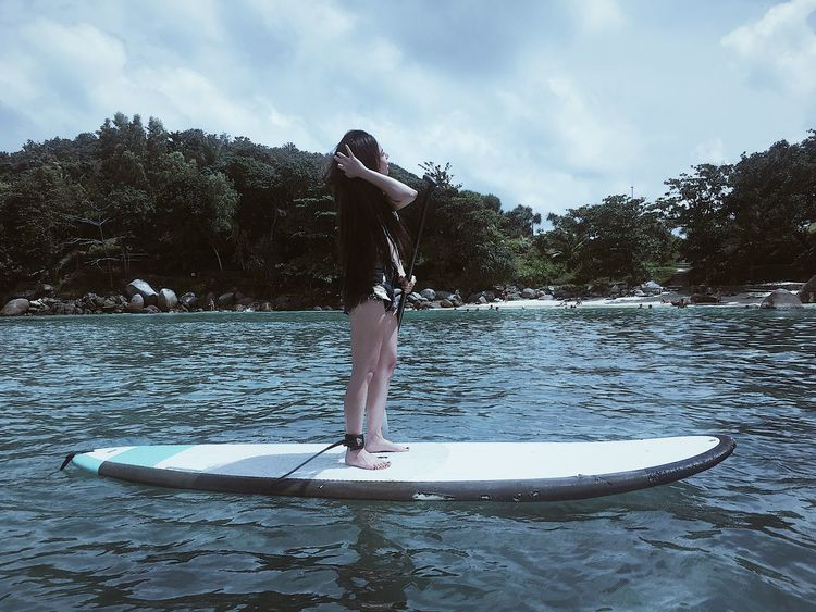 Beauty In Nature Cloud - Sky Day Full Length Leisure Activity Lifestyles Nature Nautical Vessel Oar One Person Outdoors Paddleboarding Plant Real People Sky Tree Water Waterfront Women