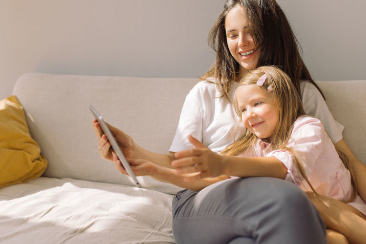 Smiling woman using digital tablet with daughter