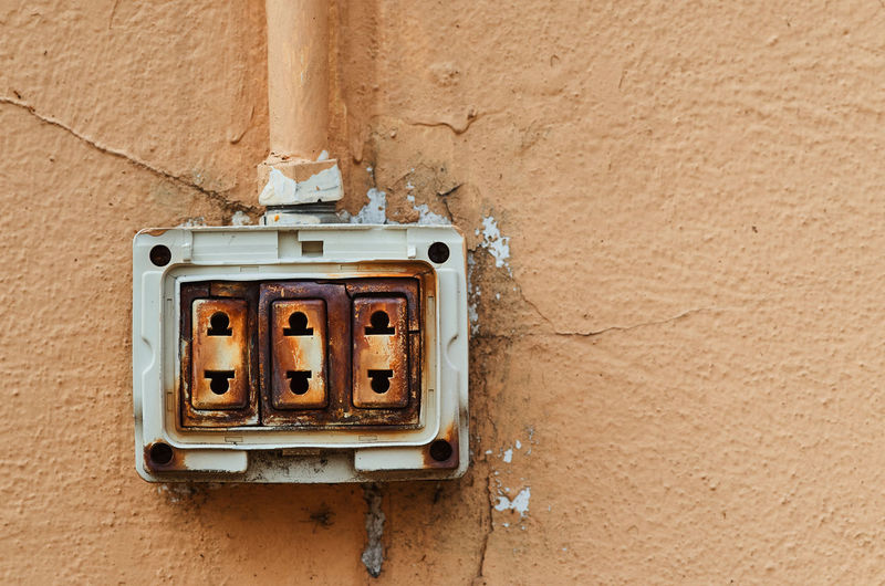 The dangerous old electric plug on wall