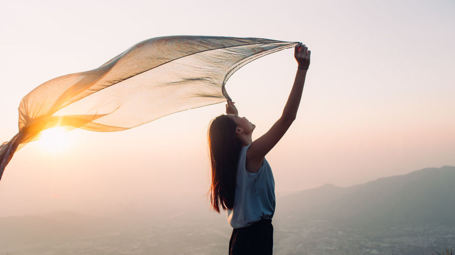 Side view of woman holding sarong against sky during sunset