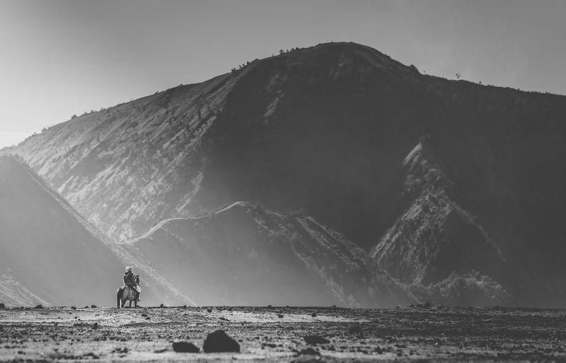 Man riding horse against mountains