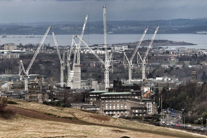 Modern construction cranes towering over traditional buildings in city centre