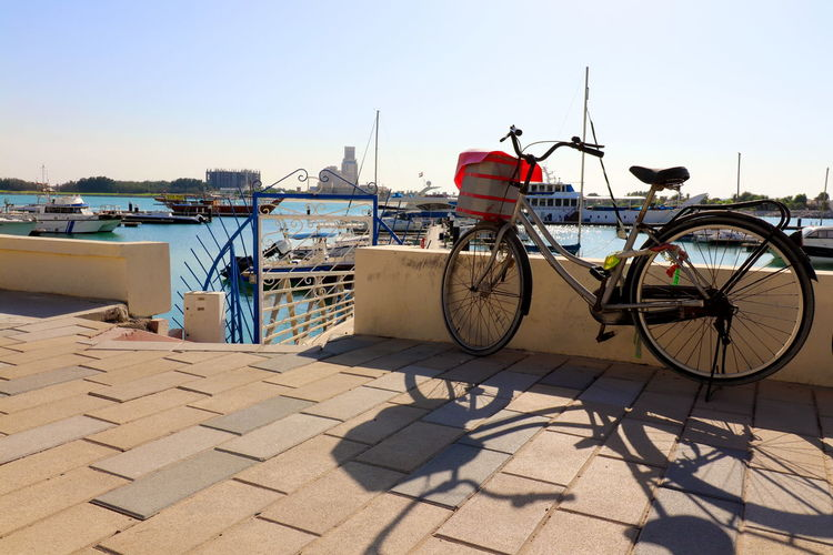 Bicycle at harbor against clear sky