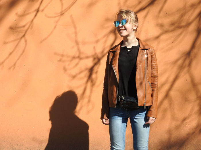 Smiling woman wearing sunglasses while standing against wall