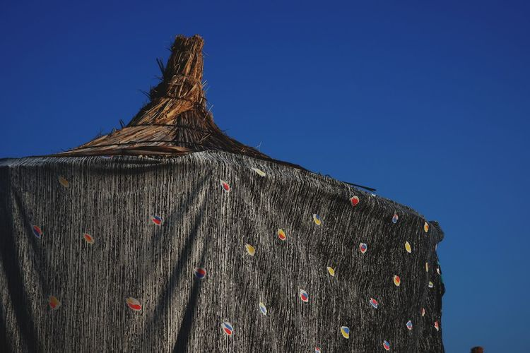 Low angle view of tree stump against clear blue sky