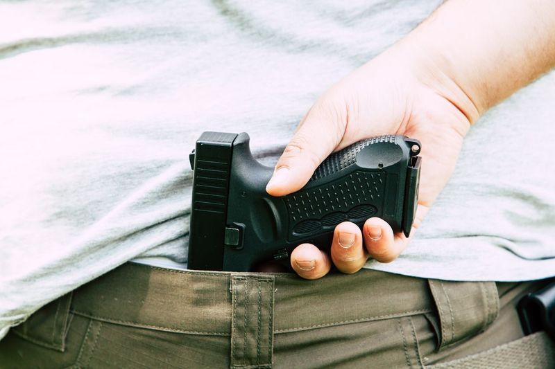 Midsection Of Man Holding Handgun