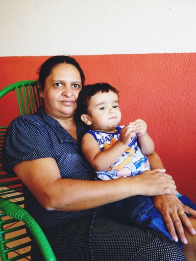 Portrait of grandmother with grandson sitting on chair against wall