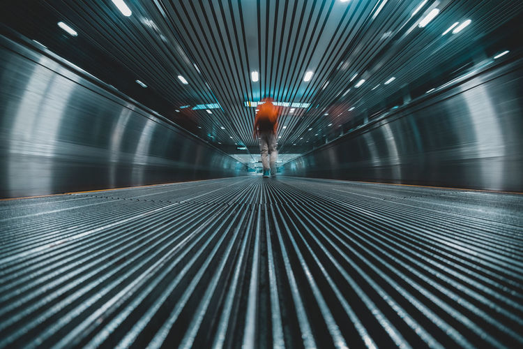 Low Angle View Metalic Motion Blur On The Way Traveling Airport Ceiling Convenience Diminishing Perspective Direction Illuminated Indoors  Lifestyles Motion Moving Walkway  Pattern The Way Forward Travel Travolator Walking Way Forward #FREIHEITBERLIN The Architect - 2018 EyeEm Awards The Traveler - 2018 EyeEm Awards HUAWEI Photo Award: After Dark