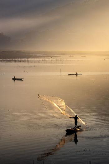 Men fishing on the lake during sunrise