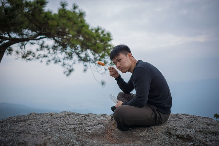 Portrait of young man eating food while sitting on cliff against cloudy sky