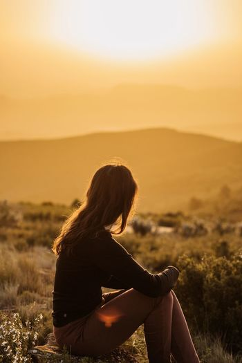 Woman looking at camera against sky during sunset