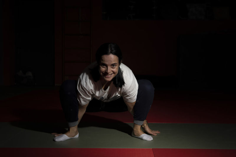 Portugal; Aula de Yoga Yogagirl Yoga Poses One Person Indoors  Lifestyles Sport Full Length Front View Real People Adult Looking Clothing Young Adult Leisure Activity Concentration Determination Healthy Lifestyle Exercising Arts Culture And Entertainment Standing Stage Black Background