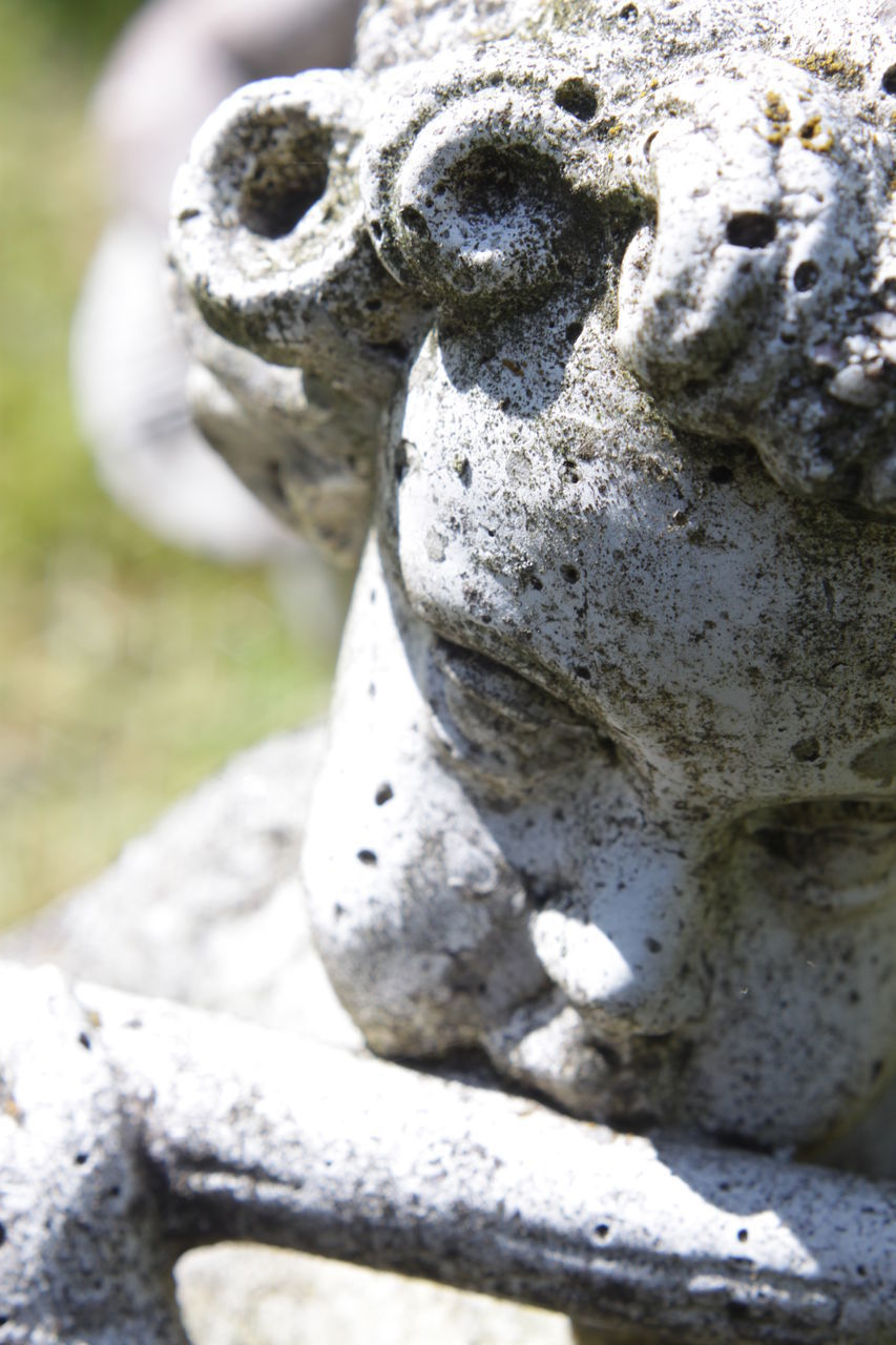 sculpture, statue, art and craft, close-up, human representation, no people, representation, day, solid, stone, nature, craft, creativity, weathered, old, stone material, outdoors, selective focus, focus on foreground, spirituality