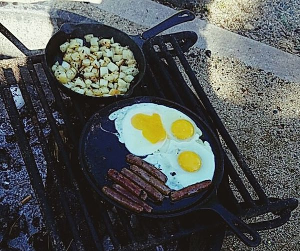 Breakfast in the mountains Sweet Moments No Reason. Just Because Fried Egg Sausages! Sausage Potatoes Food Camping Campinglife BBQing Beauty In Nature Cracked Egg Sunny Side Up Cast Iron Skillet Cast Iron Cooking Food Stories