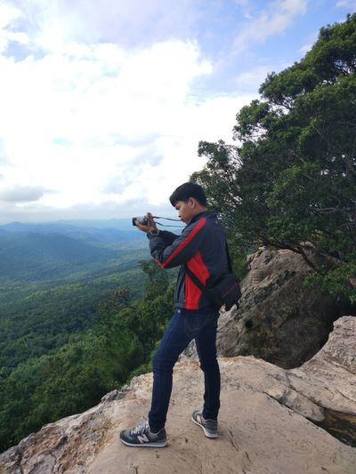 Full length of man photographing while standing on mountain against sky
