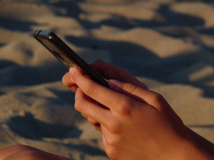 Close-up of hands using mobile phone at beach