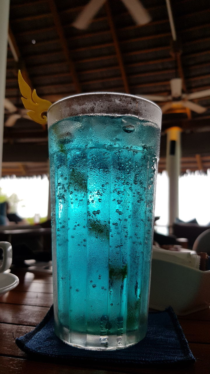 CLOSE-UP OF GLASS OF DRINK ON TABLE
