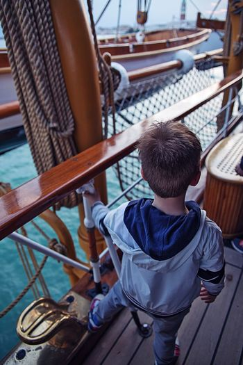 High angle view of boy standing in boat
